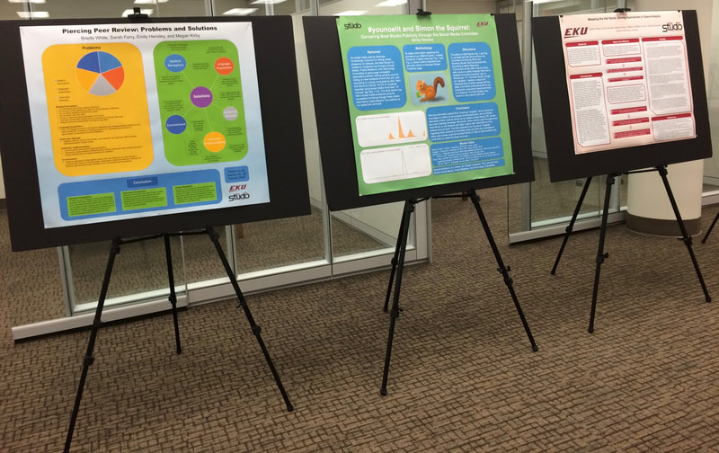 A picture of three academic research posters on display at the Noel Studio for Academic Creativity.